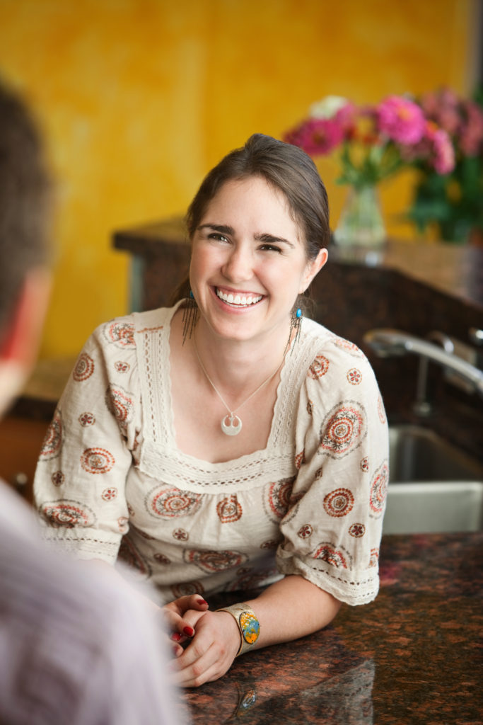 Young woman with big smile leans on granite table