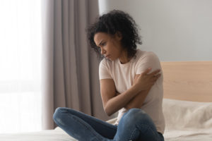 Upset depressed african woman feel sad sit alone on bed